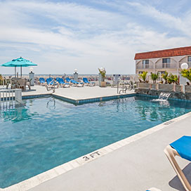 Outdoor pool with lounge chairs and ocean view at Days Inn and Suites Wildwood