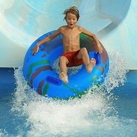 boy on an inflatable tube sliding down a water park slide