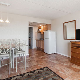 Suite living area with TV, dining table, and refrigerator